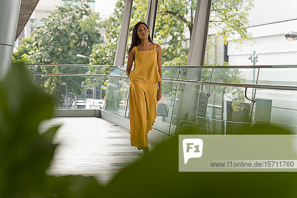 Porträt einer modisch gekleideten Frau in Gelb beim Spaziergang auf der Terrasse