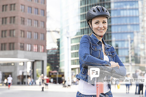 Porträt einer lächelnden Frau mit E-Scooter in der Stadt  Berlin  Deutschland