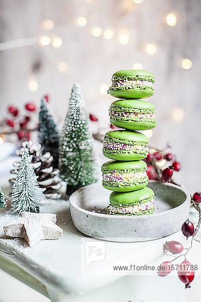 Stapel grüner Makronen und Weihnachtsschmuck