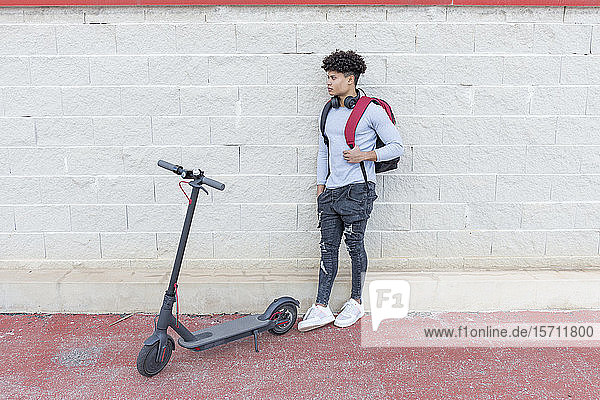 Junger Mann mit E-Scooter im Freien