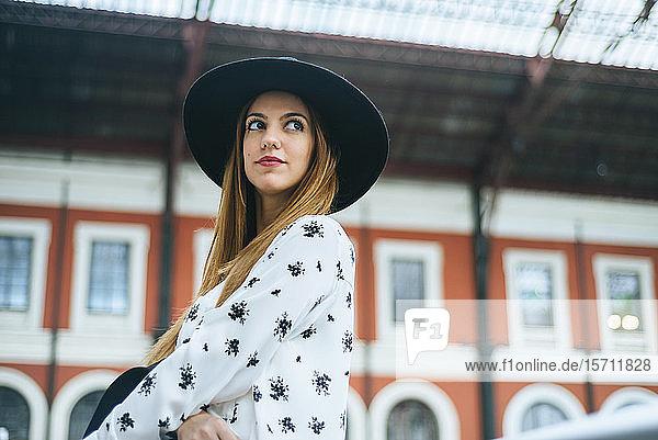 Porträt einer jungen Frau mit Hut am Bahnhof