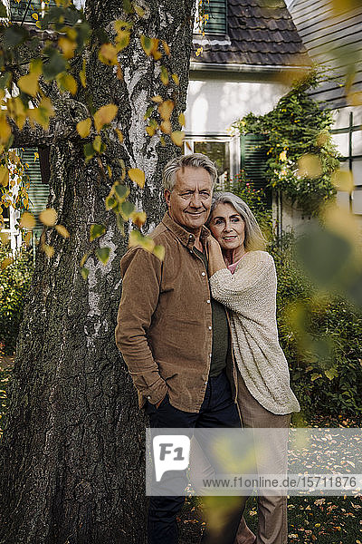 Senior couple in garden of their home in autumn