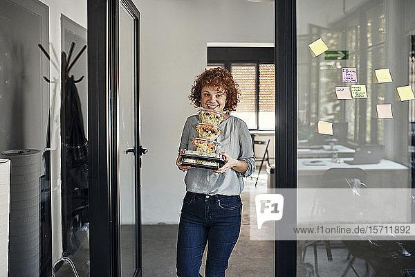 Lächelnde Geschäftsfrau serviert Essen zum Mitnehmen im Büro