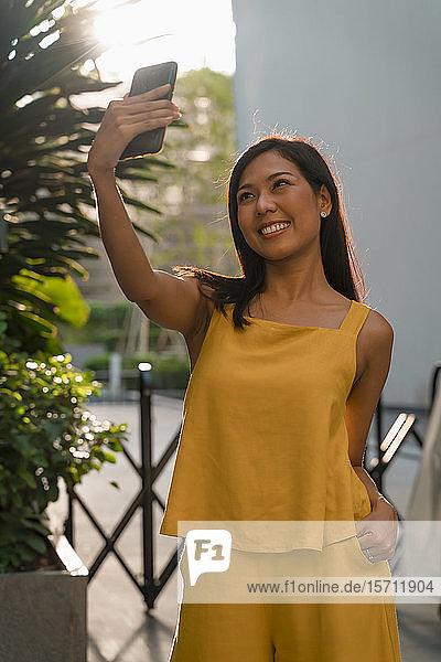 Porträt einer modischen  gelb gekleideten Frau  die sich mit einem Smartphone selbstständig macht