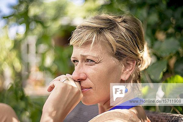 Portrait of woman in garden thinking
