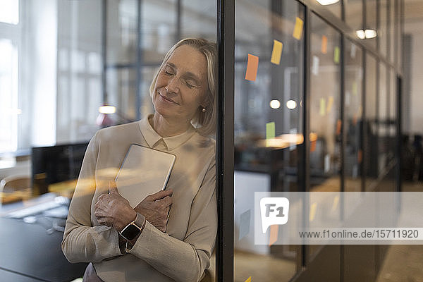 Mature businesswoman with closed eyes leaning against glass pane in office