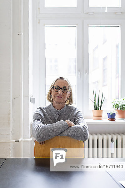 Mature businesswoman sitting on chair in office