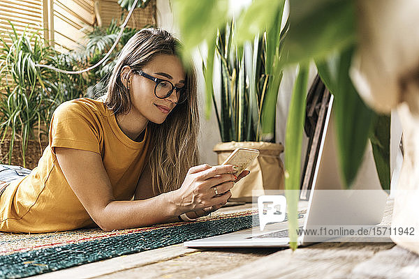 Relaxed young woman lying on the floor at home usingsmartphone and laptop