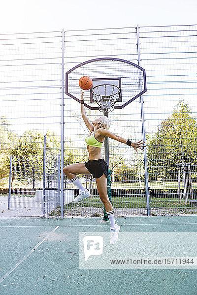 Blonde Frau spielt Basketball  taucht ein