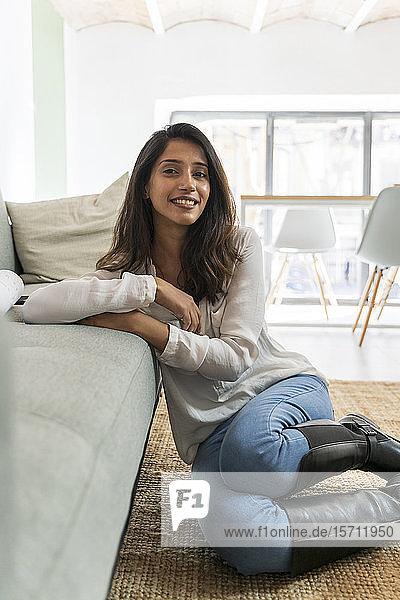 Junge indische Frau sitzt auf dem Boden und schaut in die Kamera