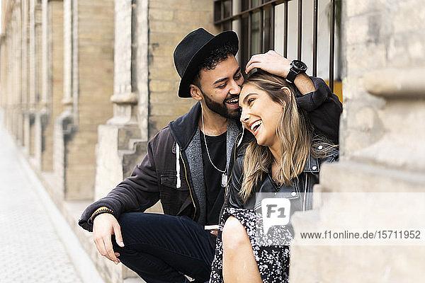 Junges Paar sitzt im Freien und amüsiert sich