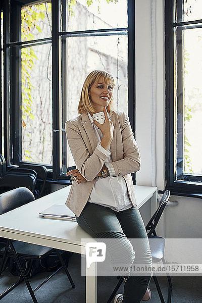 Schwangere Geschäftsfrau mit Kaffeepause im Büro