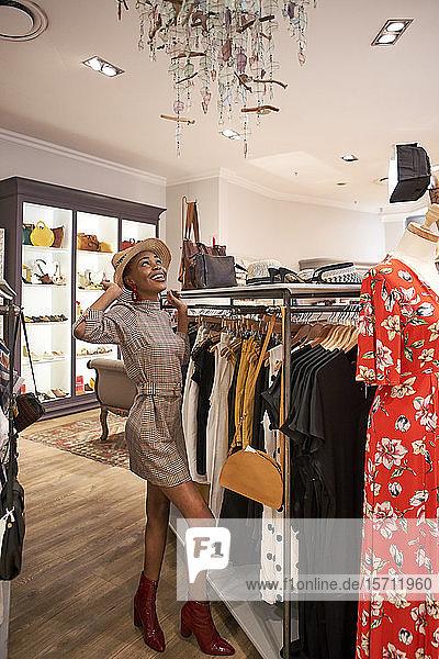 Junge Frau probiert in einem Bekleidungsgeschäft einen Hut an