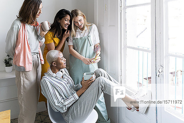 Happy women looking at cell phone at the window
