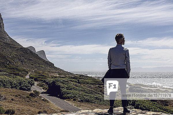 Rückenansicht eines Geschäftsmannes  der auf einem Plateau steht und auf das Meer schaut  Cape Point  Westkap  Südafrika