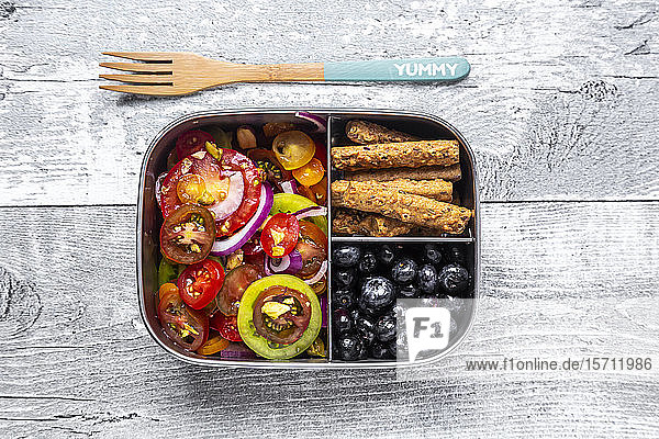 Metal box with tomato salad with red onion and pistachios  blueberries and biscuit sticks  wooden fork