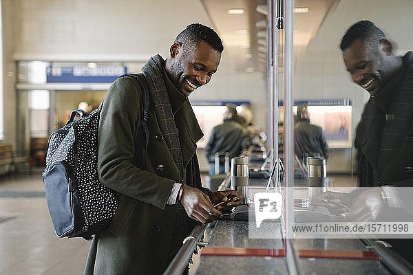 Glücklicher stilvoller Mann kauft Fahrkarte im Bahnhof
