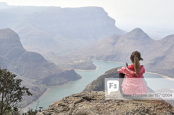 Frau sitzt auf einem Felsen und genießt die wunderschöne Landschaft unter sich  Blyde River Canyon  Südafrika.