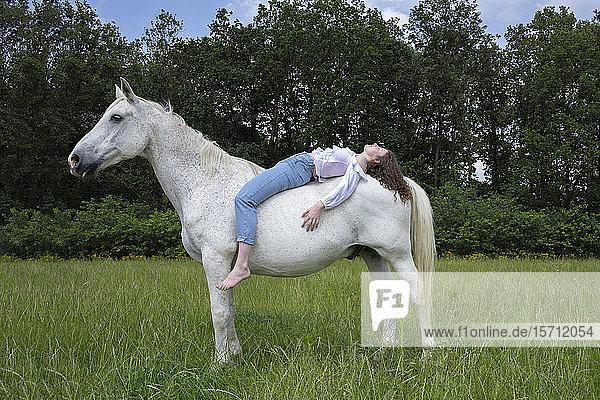 Young woman lying on back of a horse