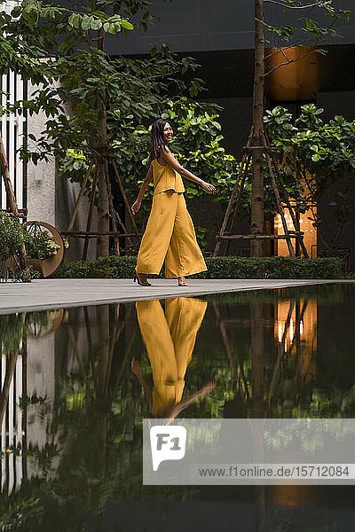 Modische Frau in gelb gekleidet tanzt in der Stadt