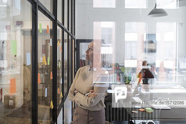 Reife Geschäftsfrau betrachtet Haftnotizen auf Glasscheibe im Büro