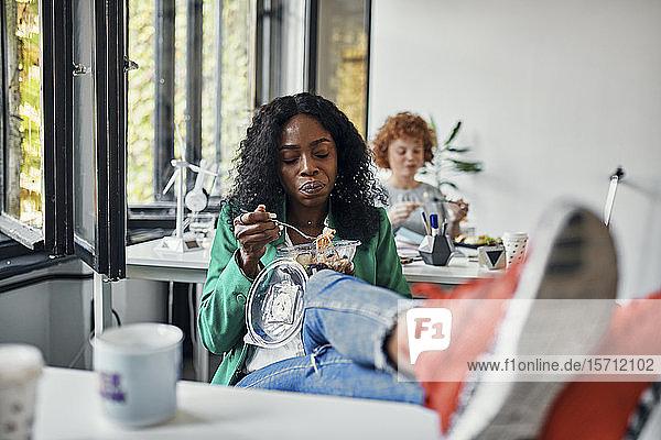 Geschäftsfrau macht Mittagspause im Büro mit den Füßen auf dem Schreibtisch