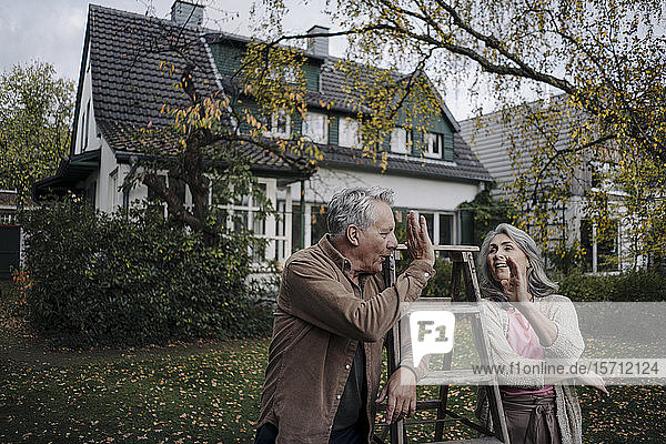Senior couple with a ladder high fiving in garden of their home