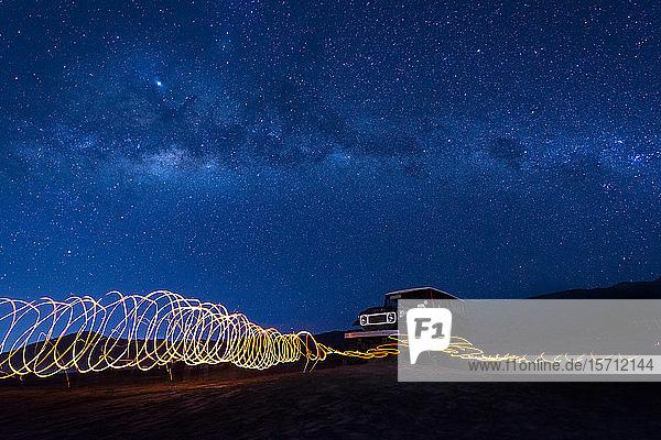 Indonesien  Ost-Java  Spiralförmige Lichtspuren vor einem nachts im Bromo Tengger Semeru-Nationalpark geparkten Auto