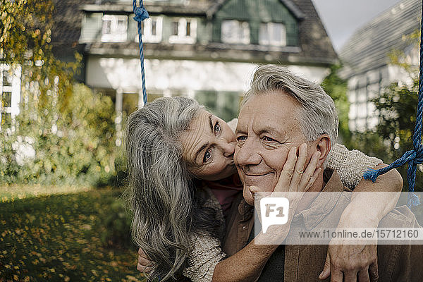 Happy woman hugging an kissing senior man on a swing in garden