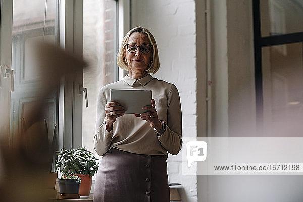 Reife Geschäftsfrau benutzt Tablett am Fenster im Büro