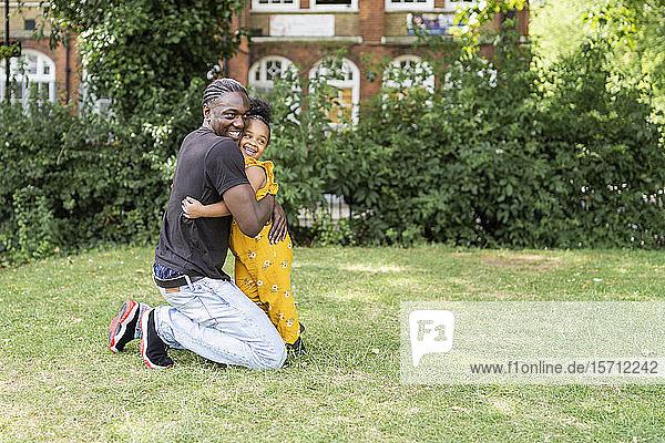 Glücklicher Vater umarmt Tochter in einem Park