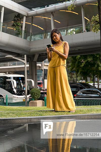 Porträt einer modischen  gelb gekleideten Frau mit Ohrstöpseln und Smartphone in der Stadt