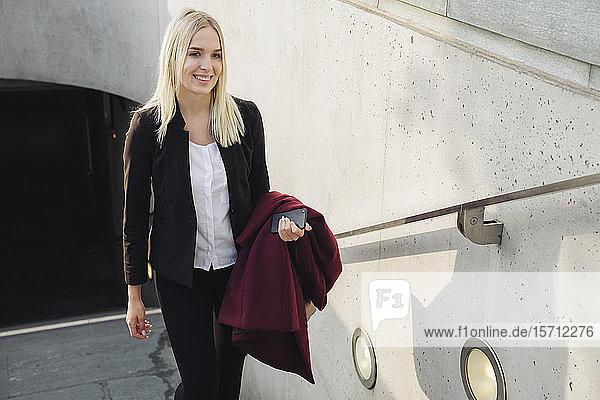 Blonde Geschäftsfrau verlässt die U-Bahn-Station