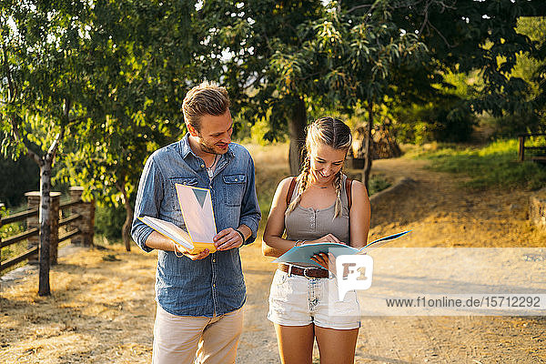 Man and woman on a field trip with folders in rural landscape