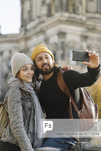Young couple taking a selfie with Berlin Cathedral in background  Berlin  Germany
