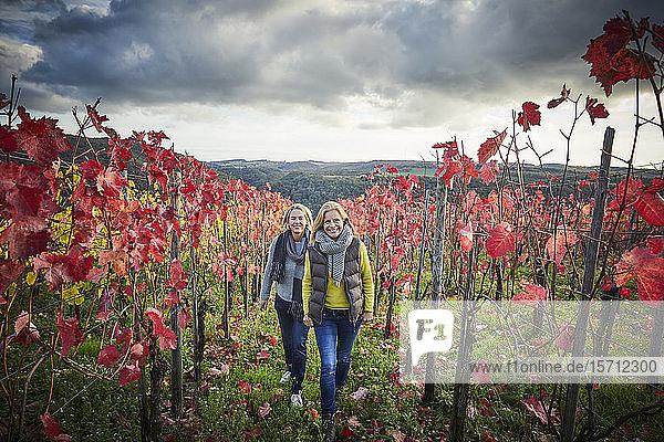 Zwei reife Frauen beim Spaziergang durch einen Weinberg