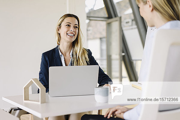 Two happy young businesswomen talking in office
