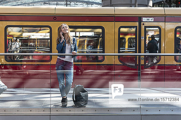 Lächelnde Frau am Telefon auf dem Bahnhof  Berlin  Deutschland