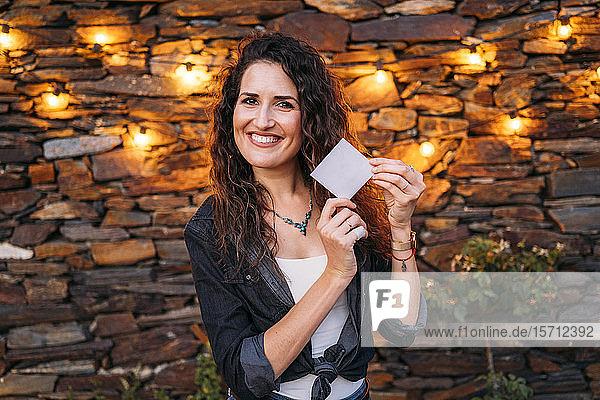 Porträt einer glücklichen Frau im Freien an einem Steinhaus mit einer leeren Karte