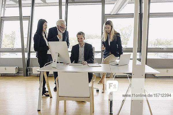 Glückliche Geschäftsleute  die eine Besprechung im Amt haben