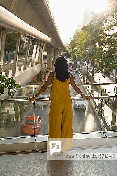 Rückenansicht einer modischen  gelb gekleideten Frau  die auf einer Brücke steht  Bangkok  Thailand