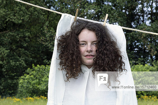 Portrait of young woman with brown ringlets in white dress drying on clothesline