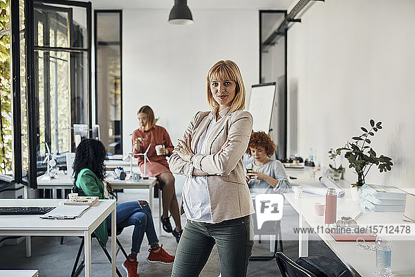 Portrait of confident pregnant businesswoman in office with colleagues in background