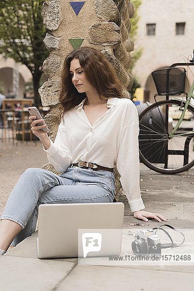 Young woman with smartphone  camera and laptop outdoors