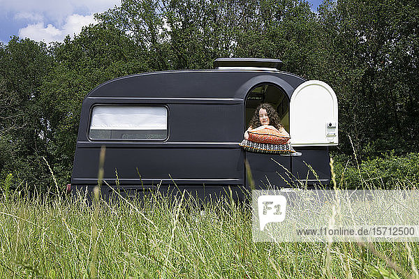 Young woman looking out of caravan standing on a meadiow