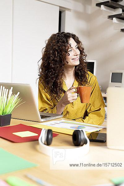 Lächelnde Frau mit Tasse Kaffee sitzt am Schreibtisch im Büro