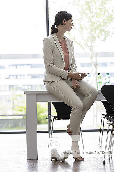 Young businesswoman with smartphone having a break in office
