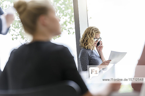 Businesswoman on the phone in office with colleagues in foreground
