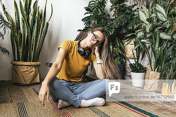 Portrait of relaxed young woman sitting on the floor at home