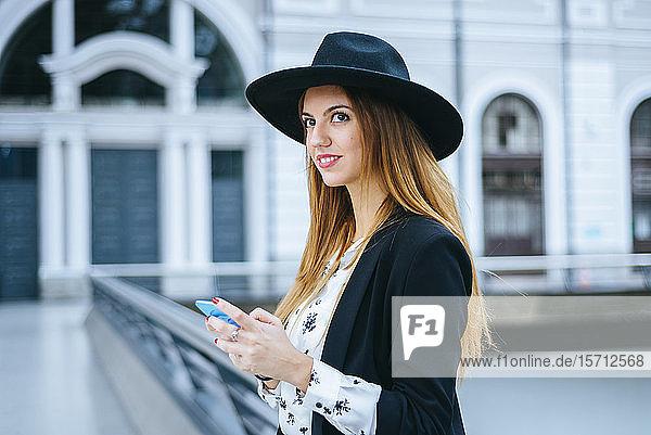 Lächelnde junge Frau mit Handy mit Hut am Bahnhof